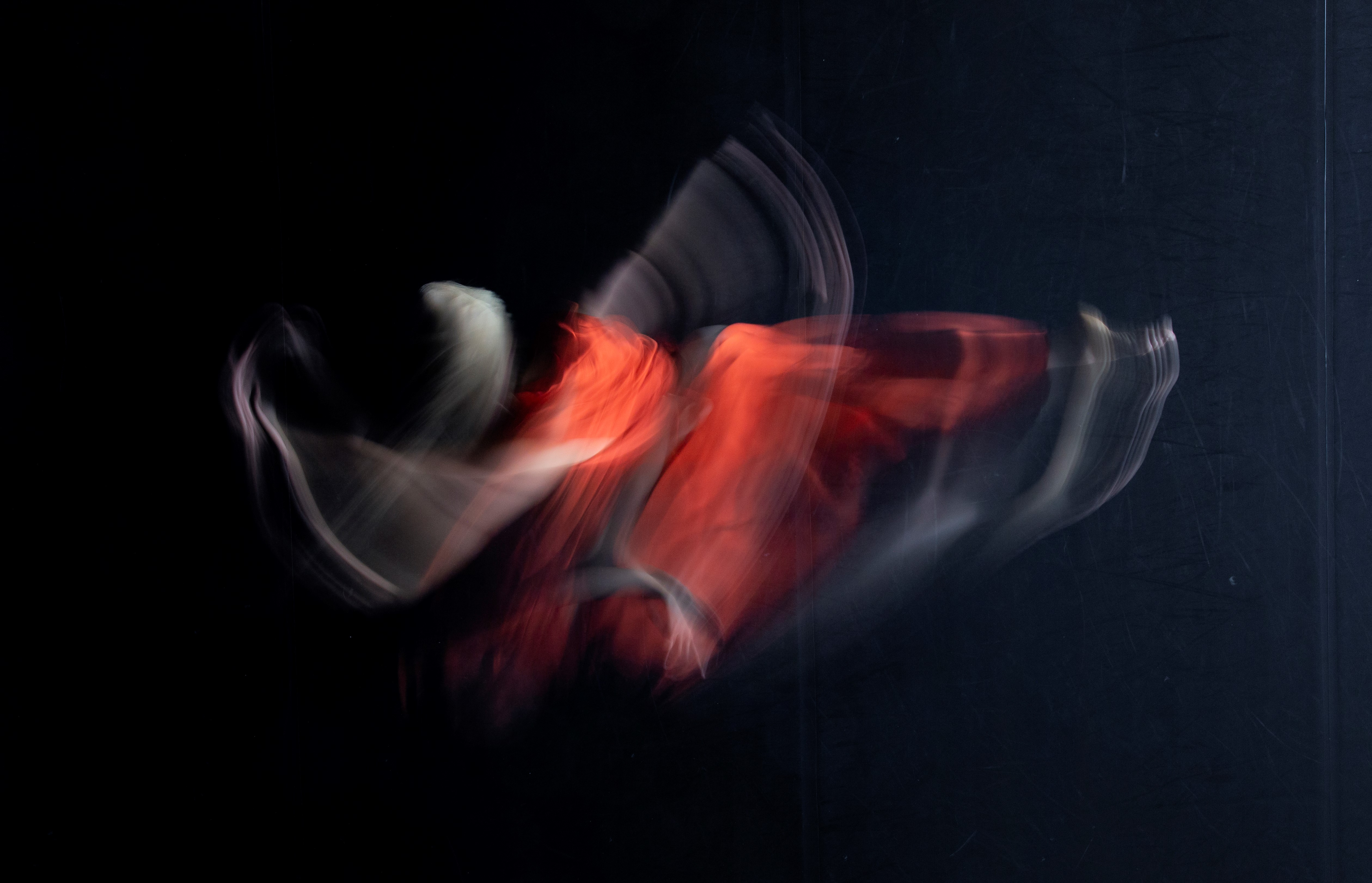 A long exposure of a dancer in a red dress with a black background. The long exposure results in the figure being almost unrecognisable, it is mostly just a blur.